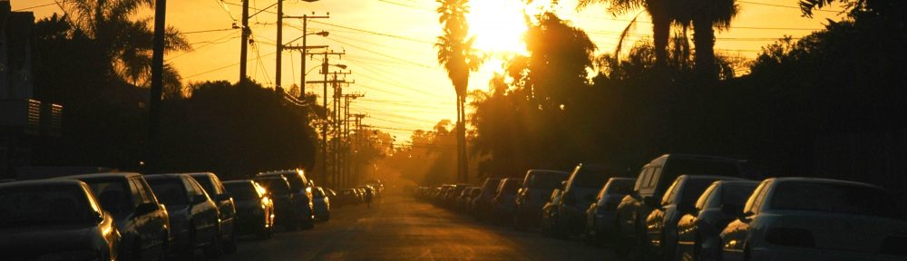 Sunset in a street lined with cars
